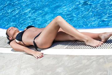 Sexy woman lying near the pool