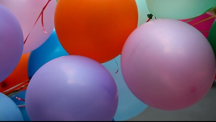bunch of colored balloons swaying in the wind