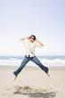 Asian man jumping on beach