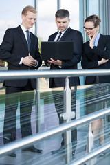 Group of business people using laptop outdoors