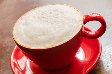 close-up of red coffee mug with frothed milk