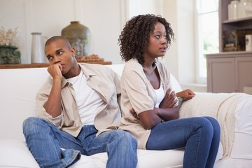 Unhappy couple arguing on the couch