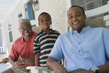 """African American grandfather, father and son on porch"""
