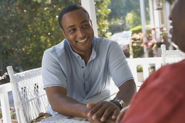 African American man sitting on porch