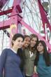 Multi-ethnic girls in front of Ferris wheel