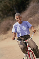 Senior African American woman riding bicycle