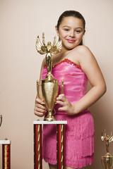 Mixed Race girl holding dancing trophy