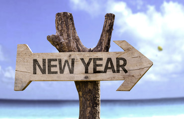 New Year wooden sign with a beach on background
