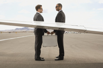 Multi-ethnic businessmen exchanging briefcase