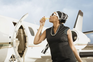 African American woman drinking champagne next to airplane