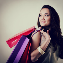 beautiful young woman holding colored shopping bags and looking