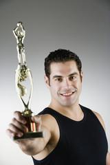 Hispanic man holding sport trophy