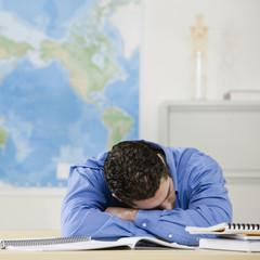 Hispanic male college student sleeping on desk