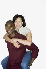 African man giving girlfriend piggyback ride