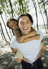 Mixed Race father giving daughter piggyback ride