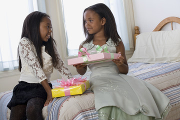 African American sisters exchanging gifts