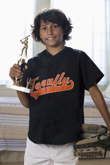 Mixed Race boy holding sports trophy