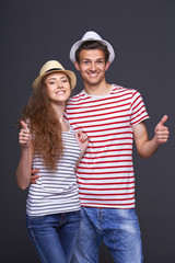 Young casual couple giving thumbs up