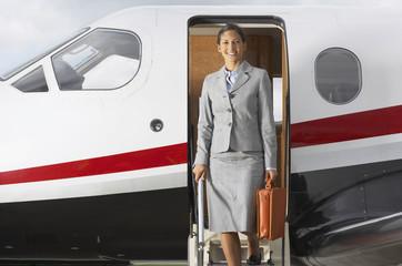 Hispanic businesswoman exiting airplane