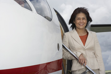 Asian businesswoman exiting airplane