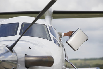 Businessman holding briefcase out of airplane