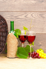 wine and fruit and wicker basket on wooden background