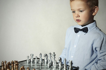 Fashionable Little boy playing chess.Smart kid.game.Chessboard