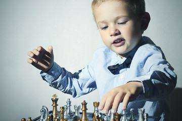 Child playing chess.Smart kid.Little genius Boy.Chessboard
