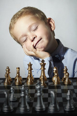 Little boy playing chess.Funny kid.Chessboard.grandmaster