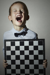 Little boy with chessboard.Children Emotion.Smile.laughter