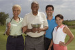 Multi-ethnic couples holding golf trophy