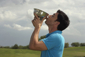 Hispanic man kissing golf trophy