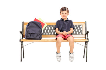 Little schoolboy sitting on a bench with a backpack