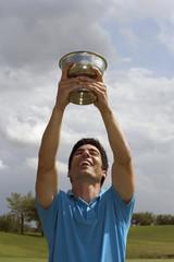 Hispanic man holding golf trophy over head