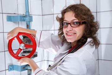 Smiling nurse holding red valve