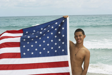 Hispanic teenaged boy holding American flag