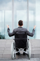 Back view of a disabled man in front of stairs