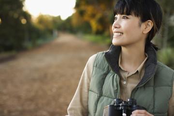 Asian woman holding binoculars
