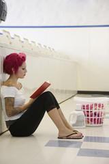 Tattooed Hispanic woman in laundromat