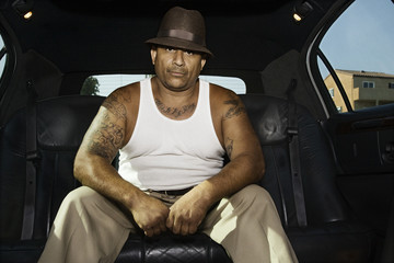 Tattooed Hispanic man in limousine