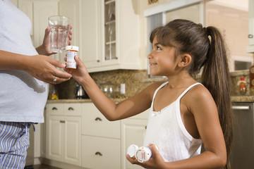 Hispanic girl handing medication to pregnant mother
