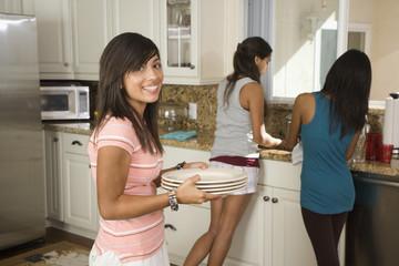 Hispanic teenaged girls washing dishes
