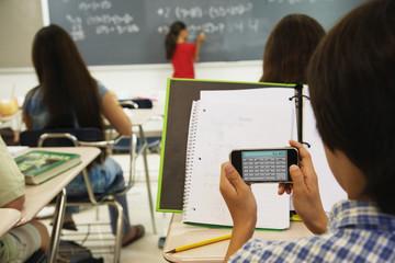 Asian boy using calculator in class