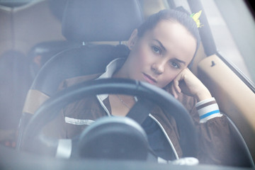Young beautiful woman at a steering wheel