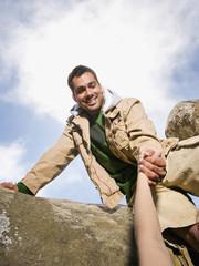 Pacific Islander man helping person climb