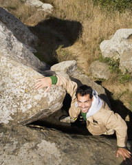 Pacific Islander man climbing rock formation