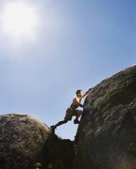 Pacific Islander man climbing rock formations