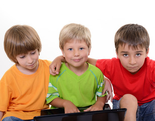 Portrait of smart schoolboys with laptop, over white