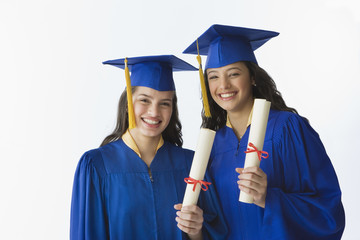 Hispanic female graduates holding diplomas