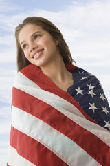 Hispanic teenaged girl wrapped in American flag